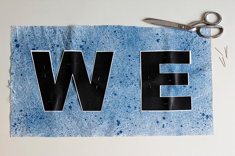 DIY: Stoffbanner - Buchstaben auf besprühten oder bemalten Stoff auflegen und mit Stecknadeln fixieren. | we love handmade